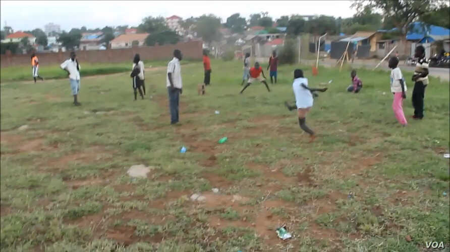 A boy takes a shot at an unseen goal on a barren field in a Juba suburb that South Sudanese children have turned into a field of football dreams.