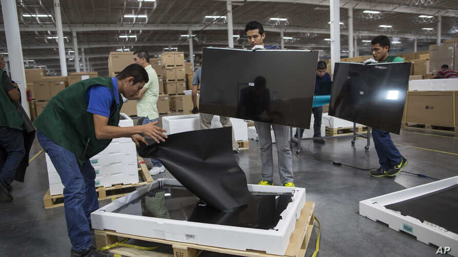 FILE - Workers check screens for faults at an LG flat screen TV assembly plant in Reynosa, Mexico, across the border from McAllen, Texas, March 23, 2017. On Jan. 5, 2019, it was announced that Mexican business and labor leaders had agreed to double t