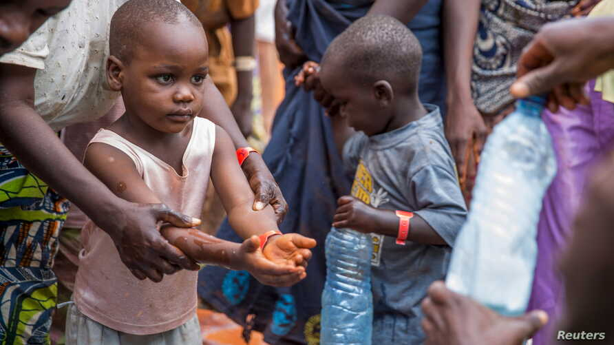 FILE - A refugee boy from Burundi who fled violence and political tension washes his hands at the Nyarugusu refugee camp in western Tanzania.