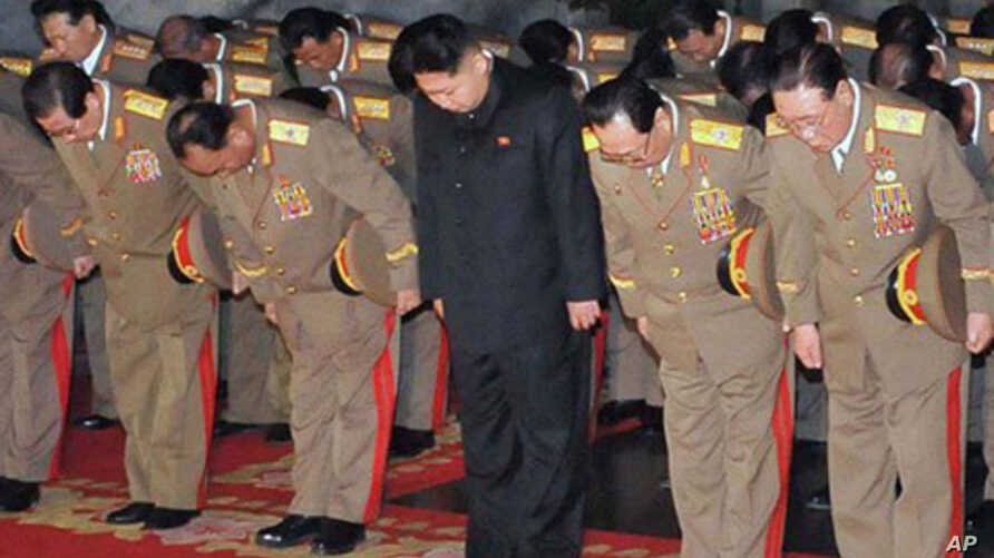 In this Saturday, Dec. 24, 2011 photo released by the Korean Central News Agency and distributed in Tokyo, Sunday, Dec. 25, 2011, by the Korea News Service, Kim Jong Un, center, North Korean leader Kim Jong Il's youngest known son and successor, visi