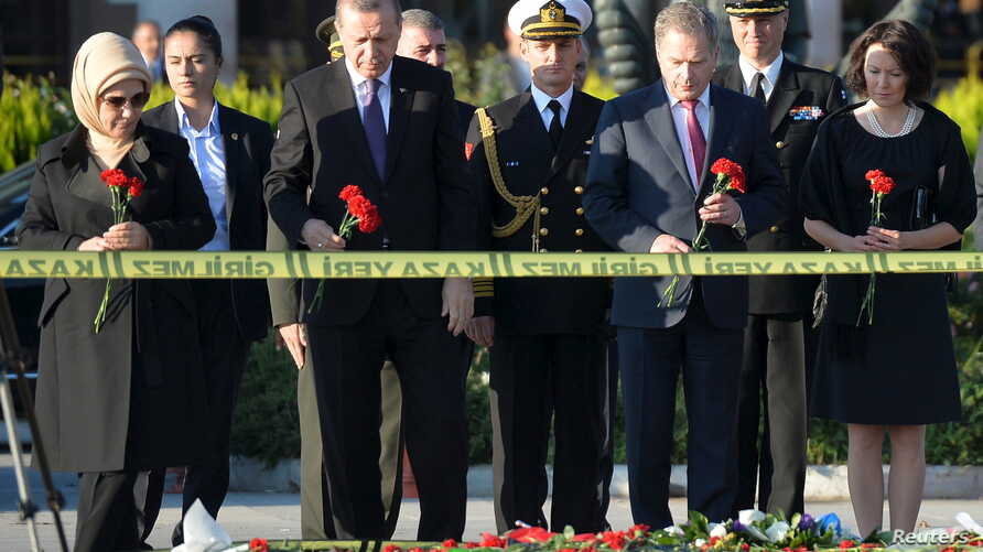 Turkish President Tayyip Erdogan (front 2nd L) and his Finnish counterpart Sauli Niinisto (front 2nd R), accompanied by their wives Emine Erdogan (L) and Jenni Haukio (R), hold carnations during a commemoration for the victims of Saturday's bombings ...