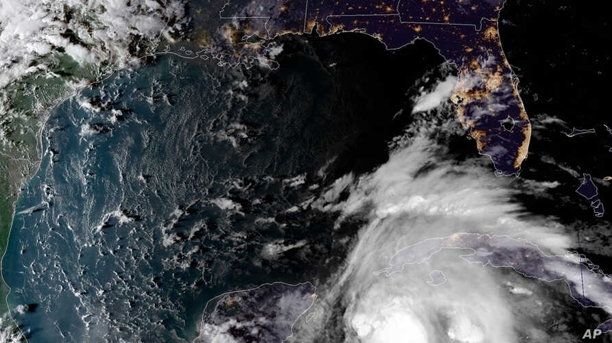 This satellite image provided by the National Oceanic and Atmospheric Administration shows a view of Tropical Storm Michael, lower right, churning as it heads toward the Florida Panhandle, Sunday, Oct. 7, 2018, at 6:52 p.m.