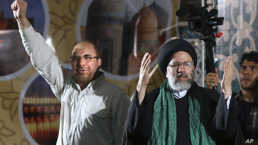 Iranian presidential candidate cleric Ebrahim Raisi, right, waves to his supporters while he is accompanied by Tehran Mayor Mohammad Bagher Qalibaf upon arrival at a campaign rally for the May 19 election at Imam Khomeini grand mosque in Tehran, Iran