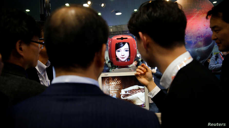FILE - Attendees interact with Commerce Bot, a robot that provides customer service with artificial intelligence technology and voice recognition, at SK telecom's stand at the Mobile World Congress in Barcelona, Spain, Feb. 28, 2017.