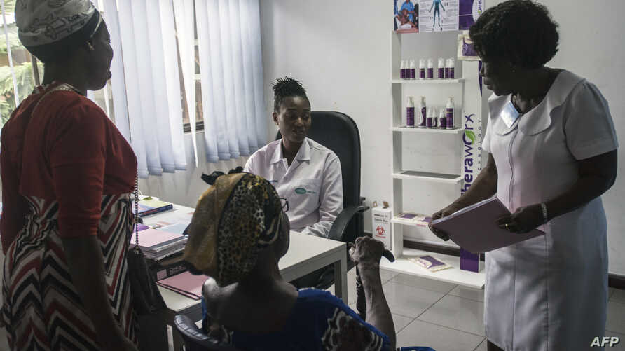 FILE - A doctor at Rabito Clinic in Accra, Ghana, takes care of a patient in her consultation room, July 3, 2018.