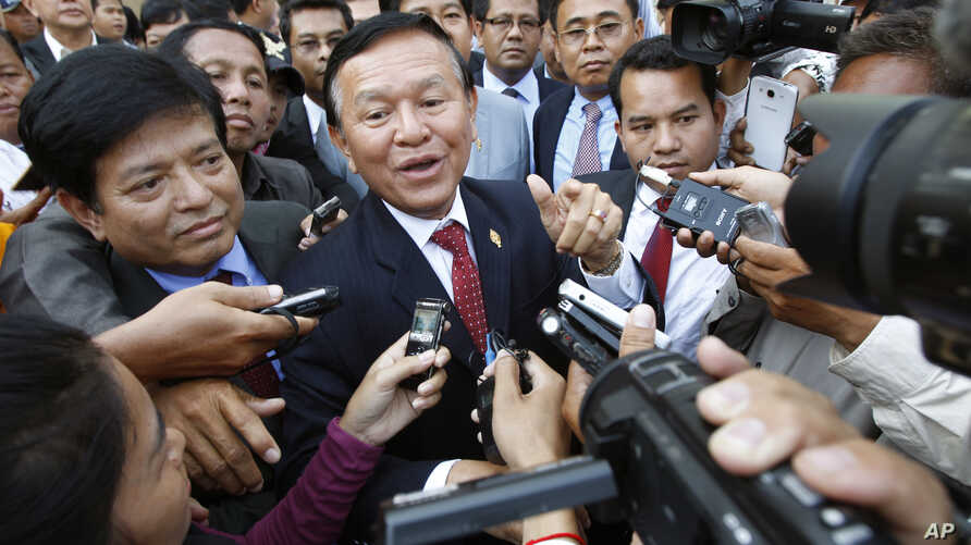 Cambodia's main opposition Cambodia National Rescue Party Deputy President and National Assembly Deputy President Kem Sokha, center, speaks to reporters outside the Phnom Penh Municipality Court in Phnom Penh, Cambodia, Wednesday, April 8, 2015. Sokh