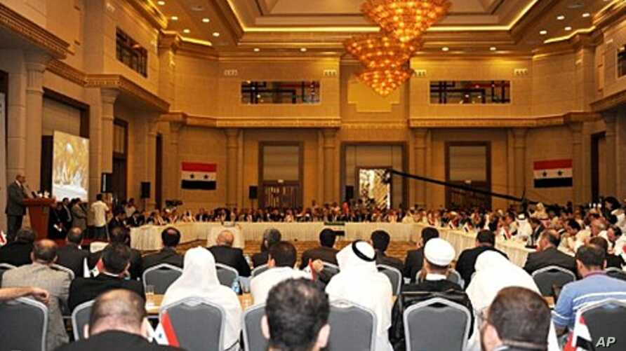 Syrian opposition leader Haitham al-Maleh (L, at podium) speaks in Istanbul, on July 16, 2011, during a meeting to discuss democratic change and voice support for a simmering revolt against President Bashar al-Assad's regime