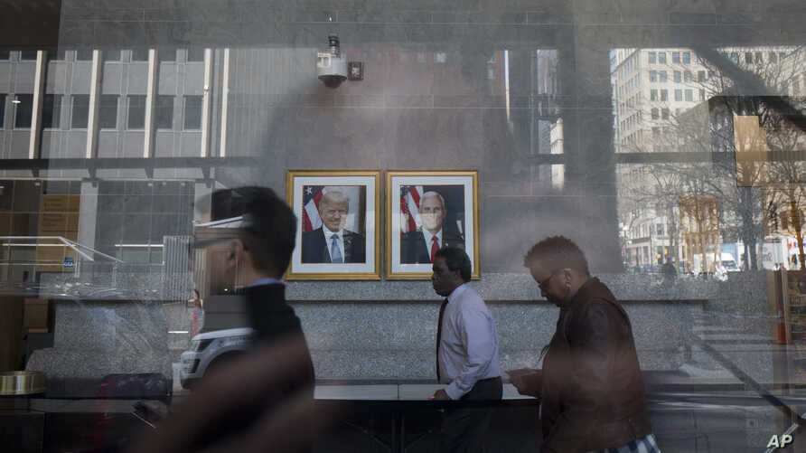Federal employees pass portraits of President Donald Trump and Vice President Mike Pence as they enter a federal office building lobby, April 24, 2018, in New York.