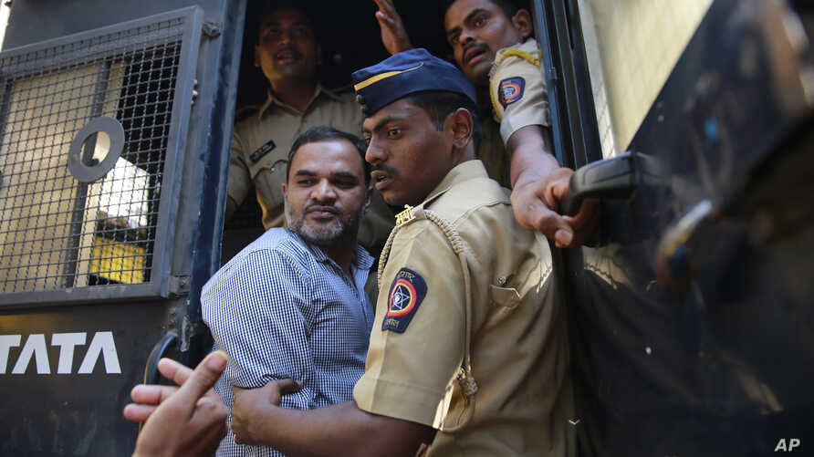 One of the men accused in the 2006 Mumbai train bombings is escorted by policemen from a prison to a court in Mumbai, India, Wednesday, Sept. 30, 2015.