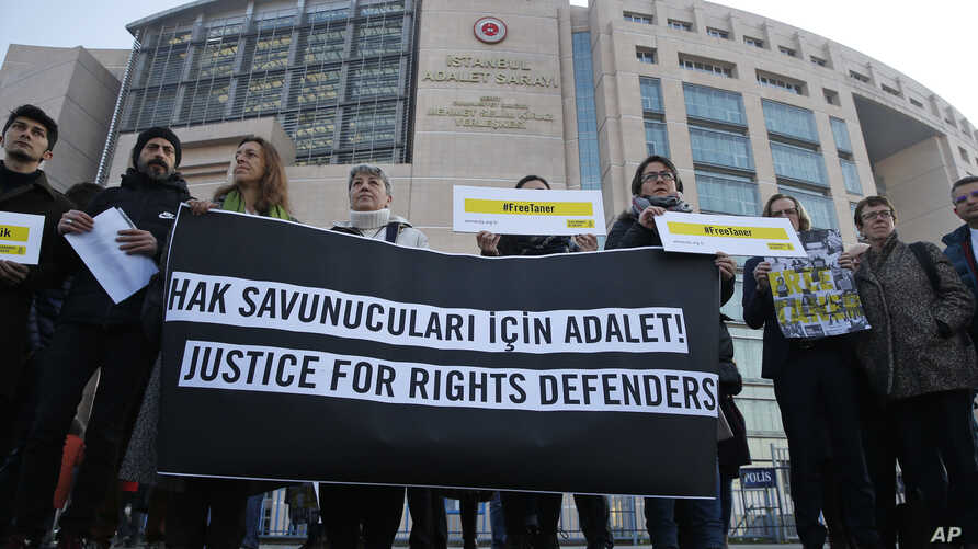 Human rights activists stage a protest outside a court in Istanbul, Turkey, Jan. 31, 2018, where a trial of eleven human rights activists, accused of belonging to and aiding terror groups, is ongoing.