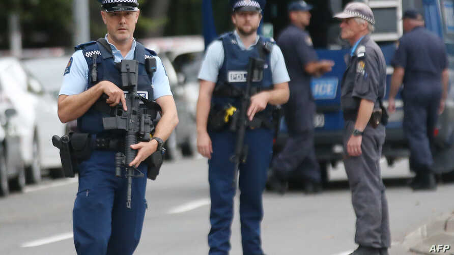 Armed police keep watch as people pay their respects in front of floral tributes for victims of the March 15 mosque  attacks, in Christchurch, March 16, 2019.