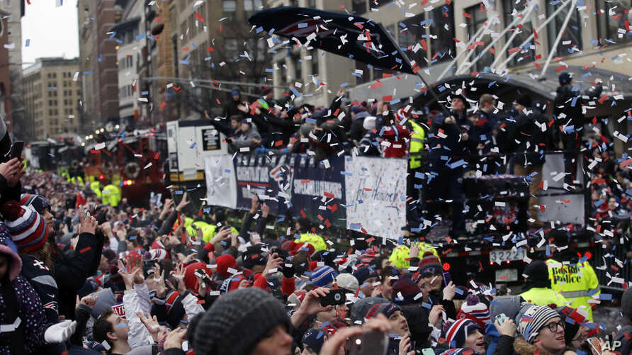 Confetti flies over fans as the New England Patriots parade through downtown Boston to celebrate theirwin over the Atlanta Falcons in Sunday's NFL Super Bowl game in Houston, Feb. 7, 2017.