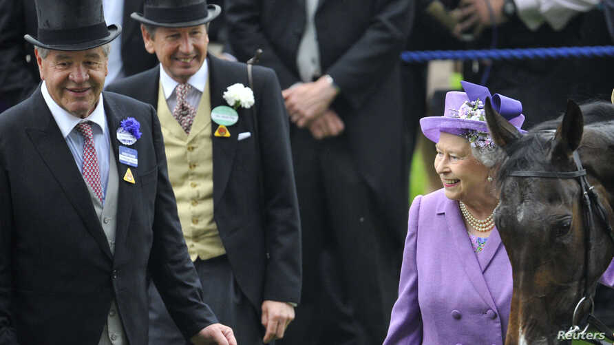 Britain's Queen Elizabeth smiles as she stands with her horse Estimate and trainer Michael Stoute, left, after it won the Gold Cup during ladies day at the Royal Ascot horse racing festival at Ascot, southern England, June 20, 2013.