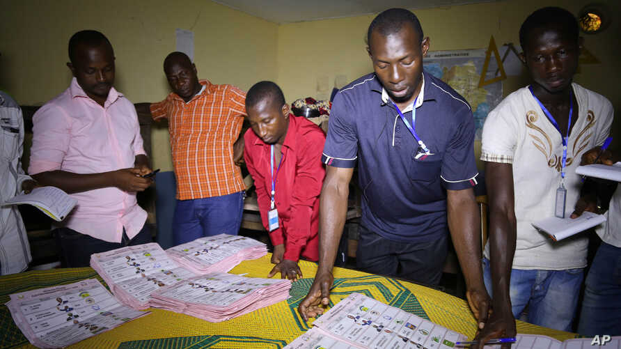 Electoral officials sort out ballot papers at the end of presidential elections in Conakry, Guinea, Oct. 11, 2015.