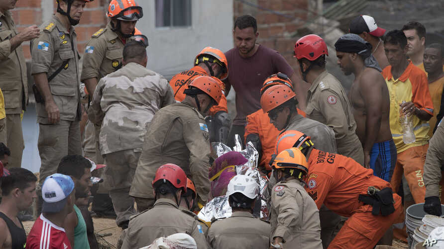 """Firefighters carry a body that was found under the debris after a mudslide in Boa Esperanca or """"Good Hope"""" shantytown in Niteroi, Brazil, Saturday, Nov. 10, 2018."""