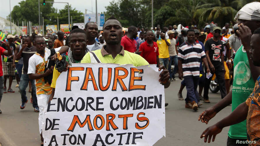 "A man holds up a sign, which reads: ""Faure still how many death by you,"" during an opposition protest calling for the immediate resignation of President Faure Gnassingbe in Lome, Togo, Sept. 6, 2017."