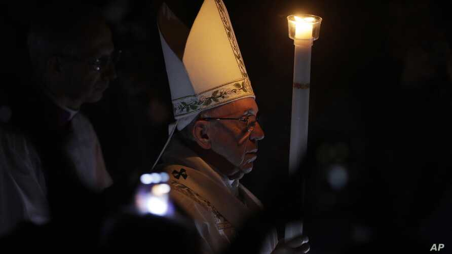 Pope Francis presides over a solemn Easter vigil ceremony in St. Peter's Basilica at the Vatican, April 15, 2017. Holding a single candle, Francis moved down the center aisle of a darkened St. Peter's Basilica, symbolizing the darkness that fell afte