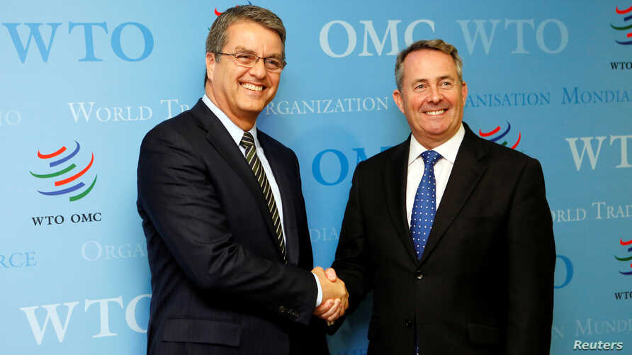 Roberto Azevedo (L), director-general of the World Trade Organization (WTO), greets Britain's International Trade Secretary Liam Fox (R) before a meeting in Geneva, Switzerland, Sept. 27, 2016.