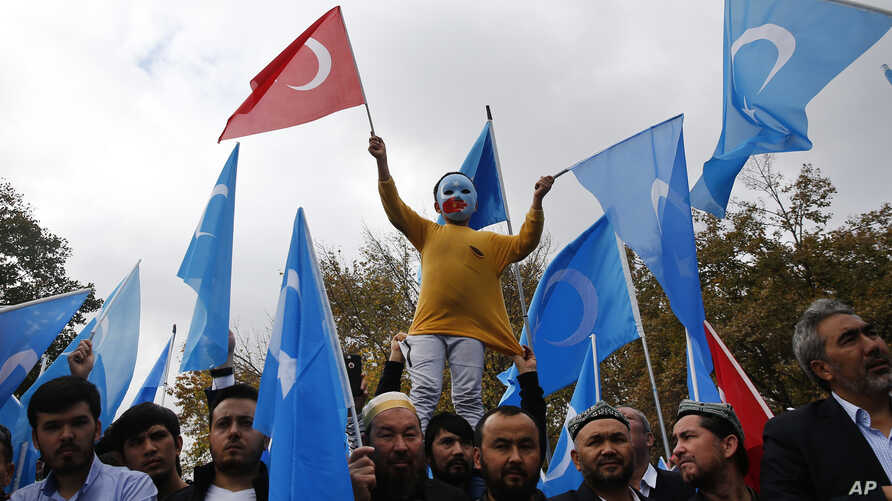 FILE - A child from the Uighur community living in Turkey, who is wearing a mask in the colors of the flag which ethnic Uighurs call East Turkestan and with a painted hand with the colors of China's flag, participates in a protest in Istanbul, Nov. 6