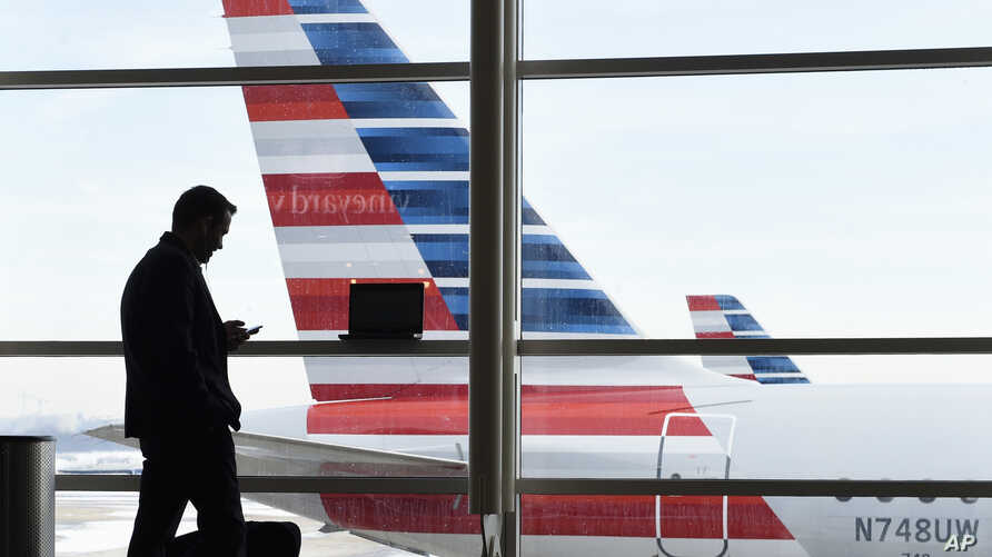FILE - A passenger talks on the phone as American Airlines jets sit parked at their gates at Washington's Ronald Reagan National Airport, Jan. 25, 2016. Numbers provided by U.S. Customs and Border Protection show a fivefold increase in electronic med...