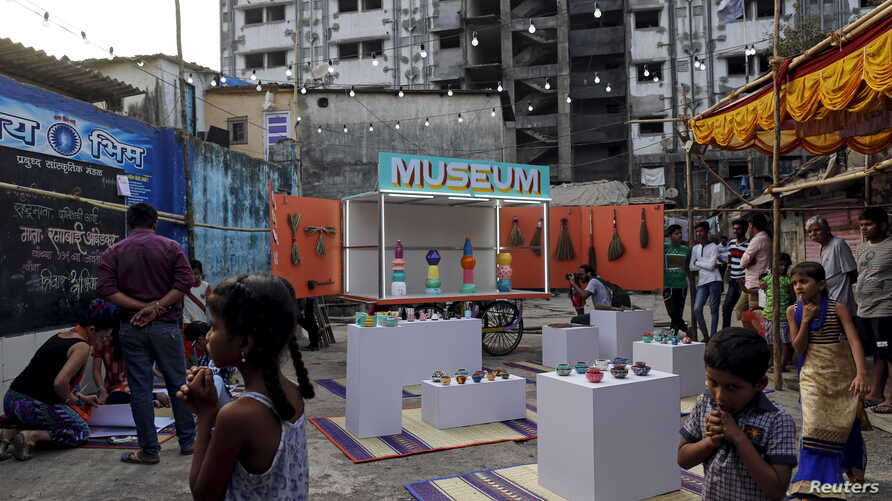 Residents gather around a mobile museum displayed on an improvised handcart in Dharavi, one of Asia's largest slums, in Mumbai, India, Feb. 18, 2016.