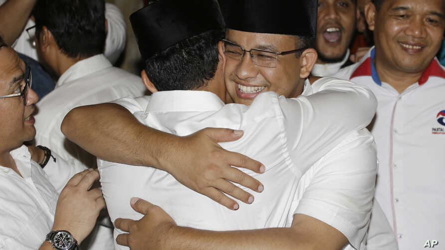 Gubernatorial candidate Anies Baswedan, center right, hugs his running mate Sandiaga Uno during a press conference in Jakarta, Indonesia, April 19, 2017.