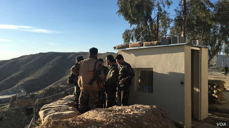 Iraqi Kurdish Peshmerga soldiers huddle around Maj. Gen. Sirwan Barzani in Makhmour, Iraq. Makhmour is expected to serve as one of the staging points for Iraqi and Peshmerga forces in the advance against the Islamic State-controlled city of Mosul, Ma...