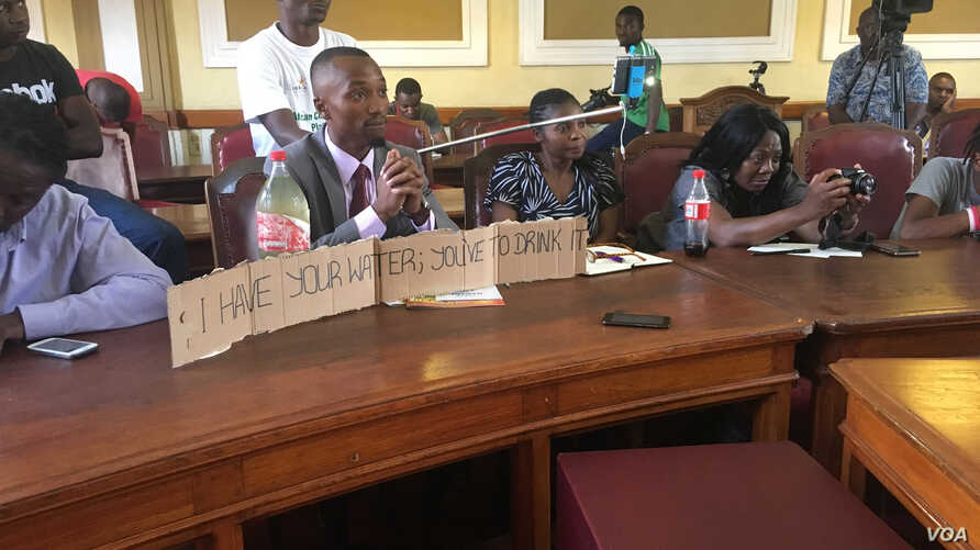 A Harare resident shows dirt water during a meeting with the Mayor at a town house meeting, Dec. 29, 2017.
