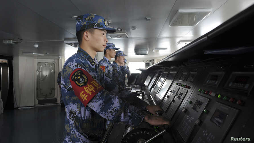 Chinese naval soldiers are pictured manning their stations on China's first aircraft carrier Liaoning, as it travels towards a military base in Sanya, Hainan province, in this undated picture made available on Nov. 30, 2013.