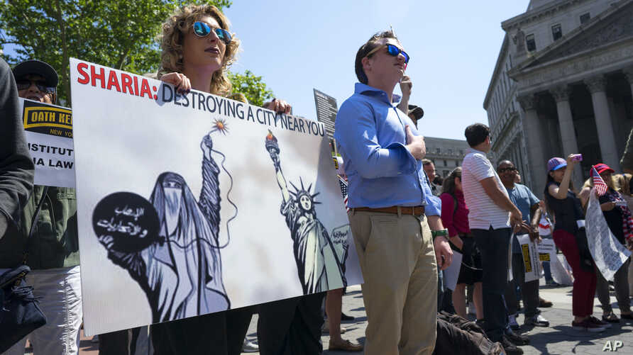 Demonstrators who gathered to protest against Islamic law take part in a rally, June 10, 2017, in New York. In more than two dozen cities across the United States, the group organizing the rallies, ACT for America, is speaking out against Shariah law