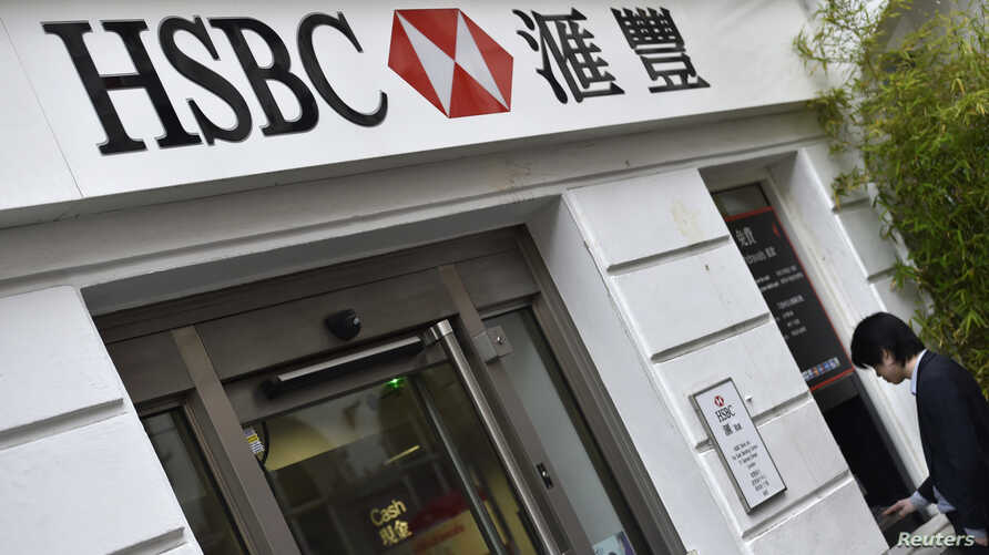 FILE - A worker uses an ATM at a branch of HSBC in Chinatown in central London, June 9, 2015.