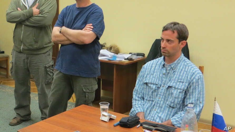 In this handout photo provided by the FSB, a man claimed by FSB to be Ryan Fogle, right, a third secretary at the U.S. Embassy in Moscow, with Embassy officials at left, sits in the the FSB offices in Moscow, early Tuesday, May 14, 2013.