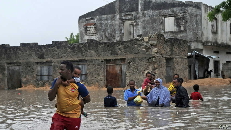 People evacuate their homes through waist-deep flood water in Mogadishu, May 20, 2018, after homes were inundated in Somalia's capital following heavy overnight rainfall.