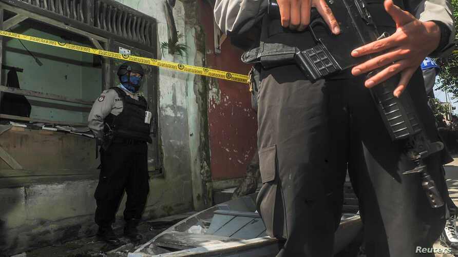 Police are seen outside the house of a person suspected of being linked to suicide bombings in Jakarta, Indonesia, May 26, 2017.