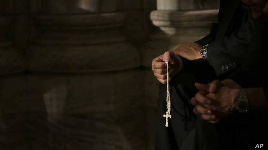 FILE - A member of the clergy prays the rosary as he waits for Pope Francis to arrive at St. Patrick's Cathedral for evening prayer service in New York, Sept. 24, 2015. Across the U.S., Catholics once faithful with their financial support to their ch