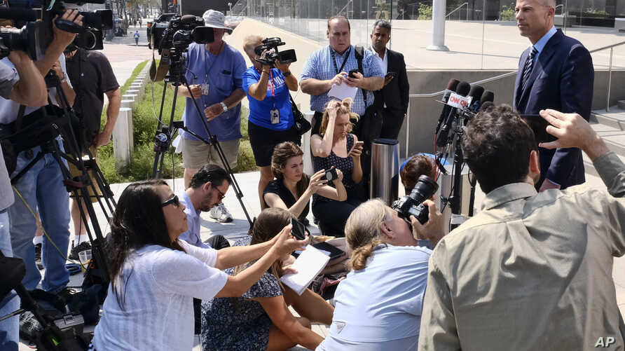FILE - Michael Avenatti (R), the attorney for porn actress Stormy Daniels talks to the media during a news conference in front of the U.S. Federal Courthouse in Los Angeles on July 27, 2018.