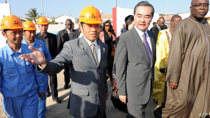 """China's Foreign Minister Wang Yi (2nd-R), flanked by Senegal's Culture Minister Abdou Azize Mbaye (R), visits the construction site of Senegal's Chinese-funded Museum of """"Civilisations Noires"""" (Black civilizations) on January 11, 2014 in Dakar. Wang"""