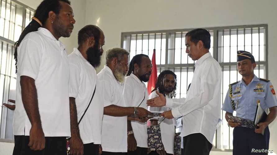 This Antara Foto photo shows Indonesia's President Joko Widodo shaking hands with and officially pardoning five political prisoners during a ceremony at a prison in Jayapura, Papua province, May 9, 2015.