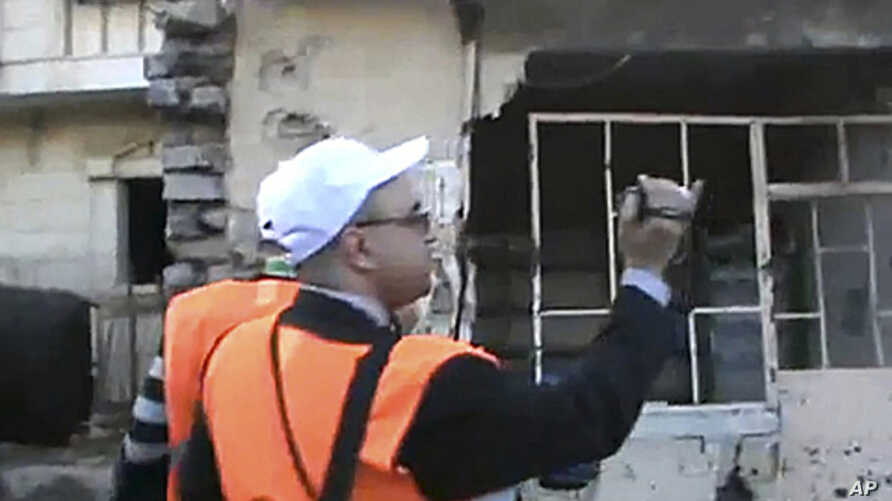 In this image made from amateur video released by Shaam News Network purports to show Arab League monitors visiting the Baba Amr area of Homs in Syria, December 28, 2011. (AP cannot independently verify the content, date, location or authenticity of