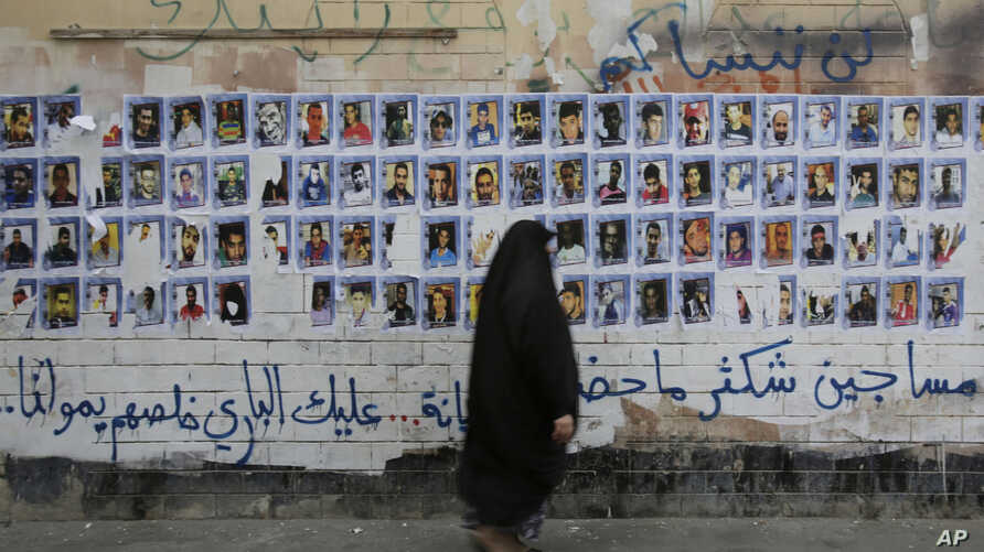 FILE - A Bahraini woman walks past images of political prisoners plastered on a wall in Sanabis, Bahrain, Oct. 22, 2015. Prosecutors in Bahrain said May 15, 2018 that a court has revoked the citizenship of 115 people in a mass terrorism trial.