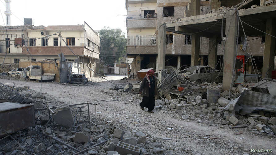 A man walks on rubble at a damaged site in the rebel held besieged town of Hamouriyeh, eastern Ghouta, near Damascus, Syria, Feb. 21, 2018.