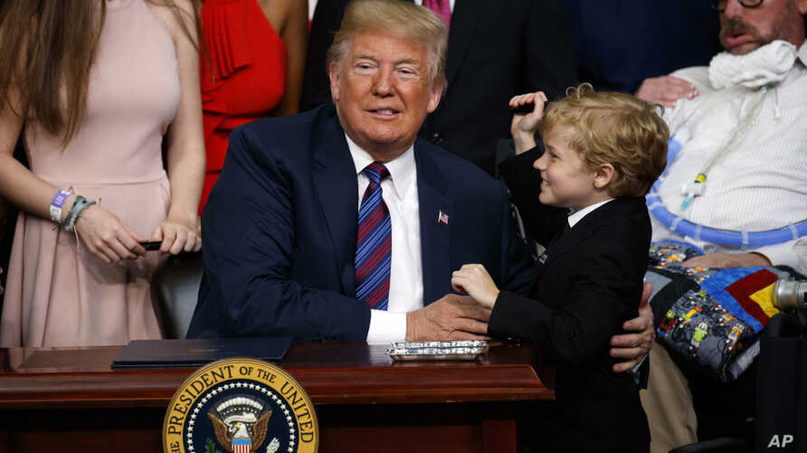 "President Donald Trump hugs Jordan McLinn, a Duchenne muscular dystrophy patient, after signing ""right to try"" legislation in the South Court Auditorium on the White House campus, May 30, 2018, in Washington."