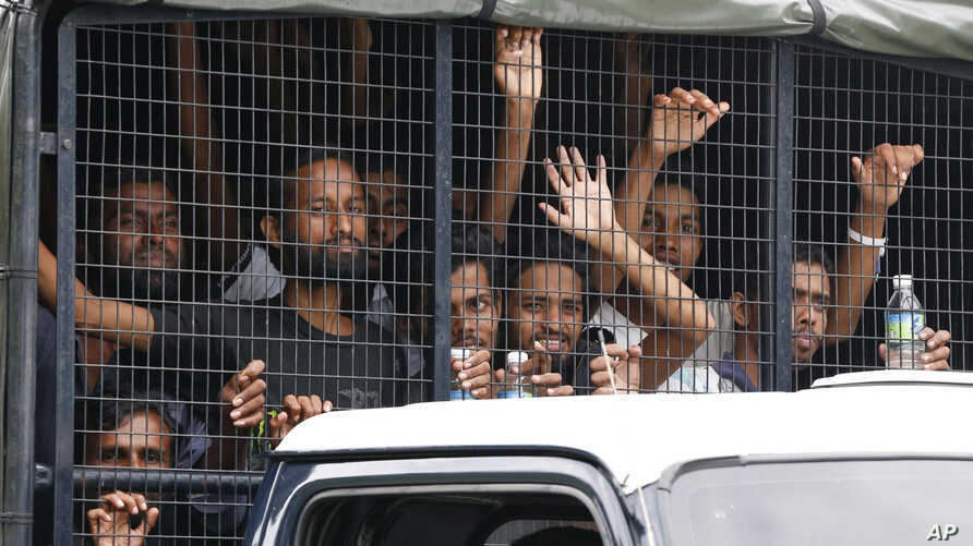 Migrants ride on a truck as they are transferred from a temporary detention facility to a naval base on Langkawi island, Malaysia, on Wednesday, May 13, 2015.
