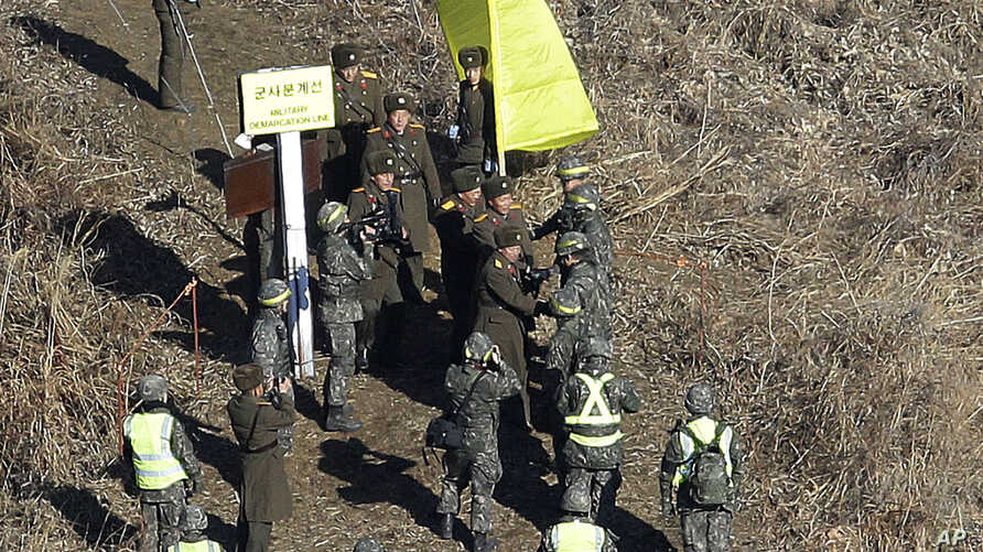 North Korean army soldiers, top, are greeted by South Korean army soldiers, wearing helmets, as they cross the Military Demarcation Line inside the Demilitarized Zone (DMZ) to inspect the dismantled South Korean guard post in the central section of t