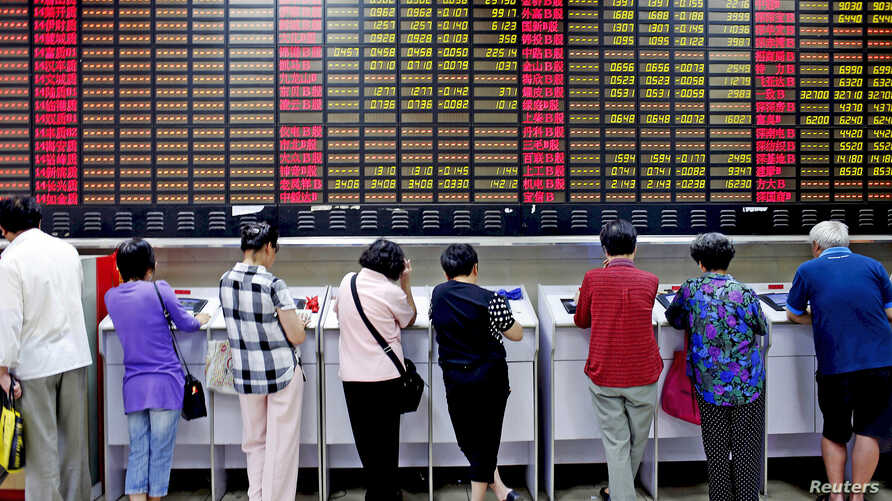 Investors look at computer screens showing stock information at a brokerage house in Shanghai, China, July 8, 2015.