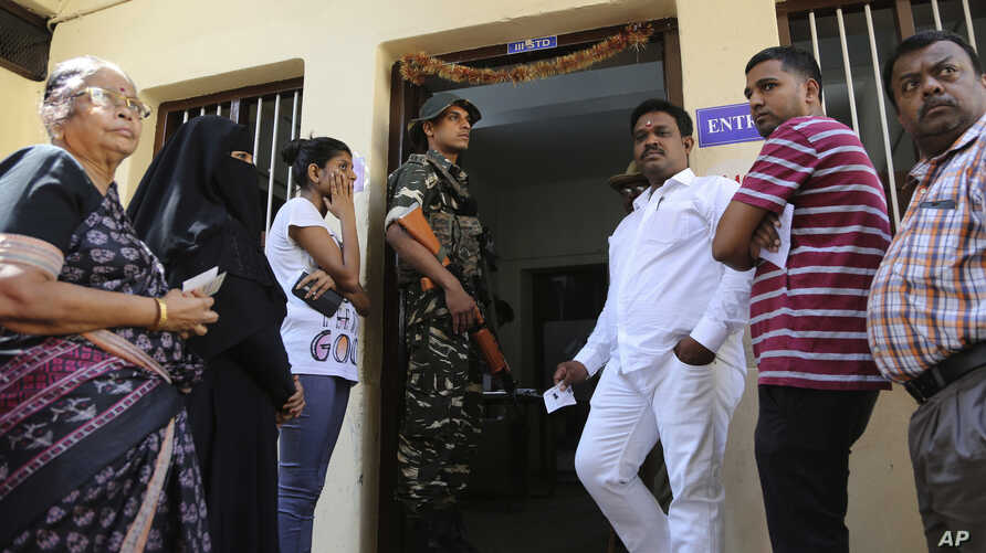 An Indian paramilitary soldier stands guard as voters wait at a polling station in Bangalore, India, May 12, 2018. India's southern state of Karnataka headed to the polls to elect 224 lawmakers.