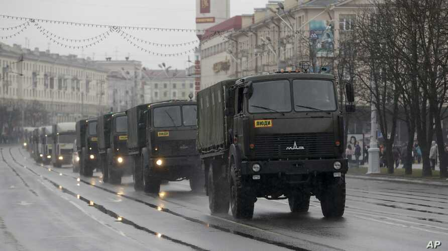 Police vehicles drive through a street during an opposition rally in Minsk, Belarus, March 25, 2017. A cordon of club-wielding police blocked the demonstrators' movement along Minsk's main avenue near the Academy of Science. Hulking police detention