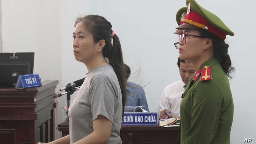 Prominent blogger Nguyen Ngoc Nhu Quynh, left, stands trial in the south central province of Khanh Hoa, Vietnam, Thursday, June 29, 2017. She was accused of distorting government policies and defaming the Communist regime on her Facebook posts, her l