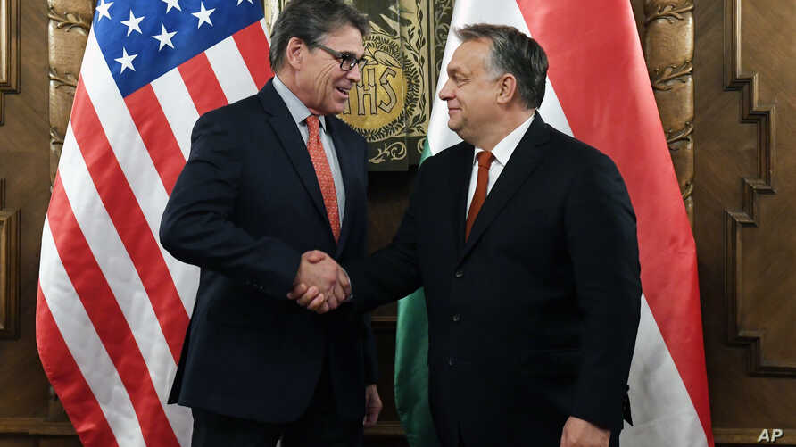 Hungarian Prime Minister Viktor Orban, right, shakes hands with U.S. Energy Secretary Rick Perry during their meeting in Orban's office in the Parliament building in Budapest, Hungary, Nov. 13, 2018.
