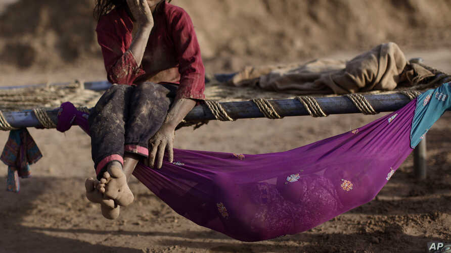 Pakistani Naginah Sadiq, 5, who works in a brick factory, rests on a bed next to her sister Shahzadi, 8 months, sleeping in a hammock attached to the bed, on World Day Against Child Labor, on the outskirts of Islamabad, Pakistan, June 12, 2012.